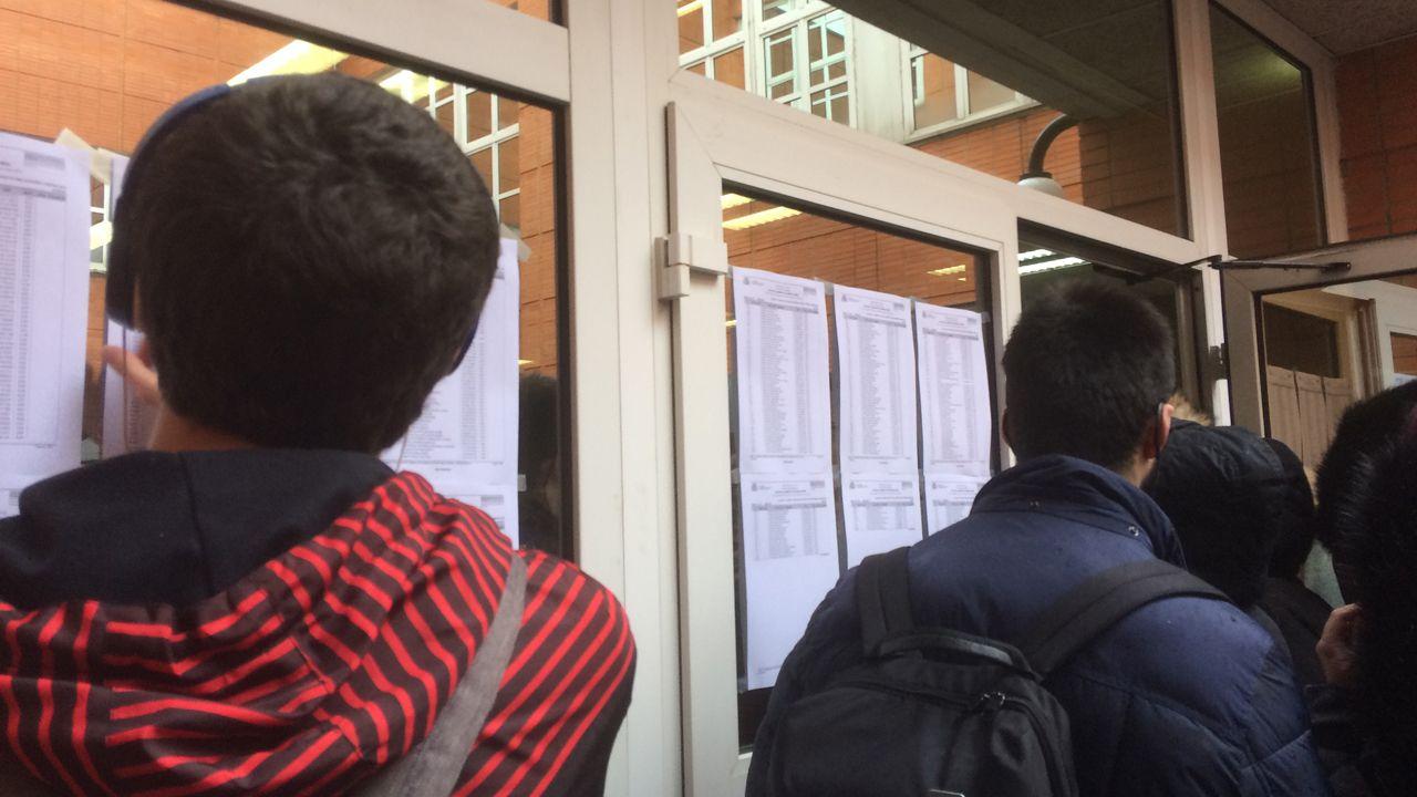 Estudiantes ojeando el listado de aulas en el examen MIR en Oviedo