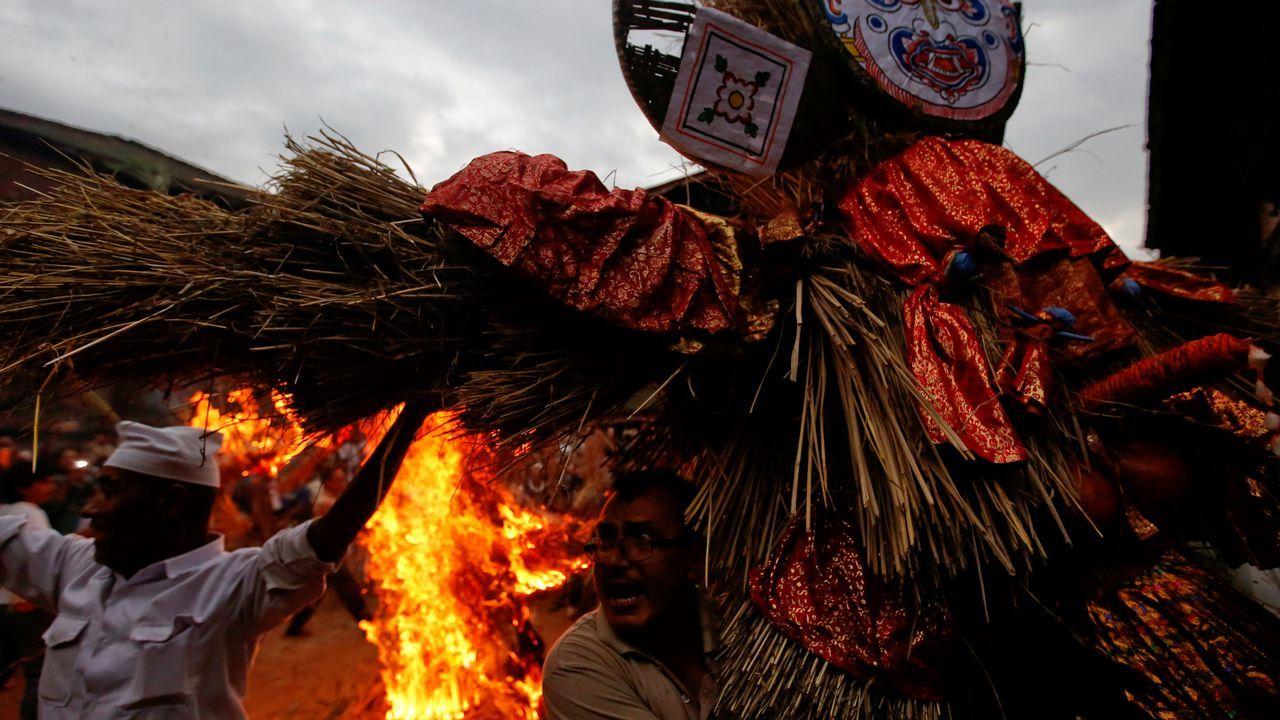 La gente lleva una efigie del demonio Ghantakarna mientras otra efigie de un demonio se quema para simbolizar la destrucción del mal y la creencia de conducir espíritus malignos y fantasmas, durante el festival Ghantakarna en la antigua ciudad de Bhaktapur, Nepal