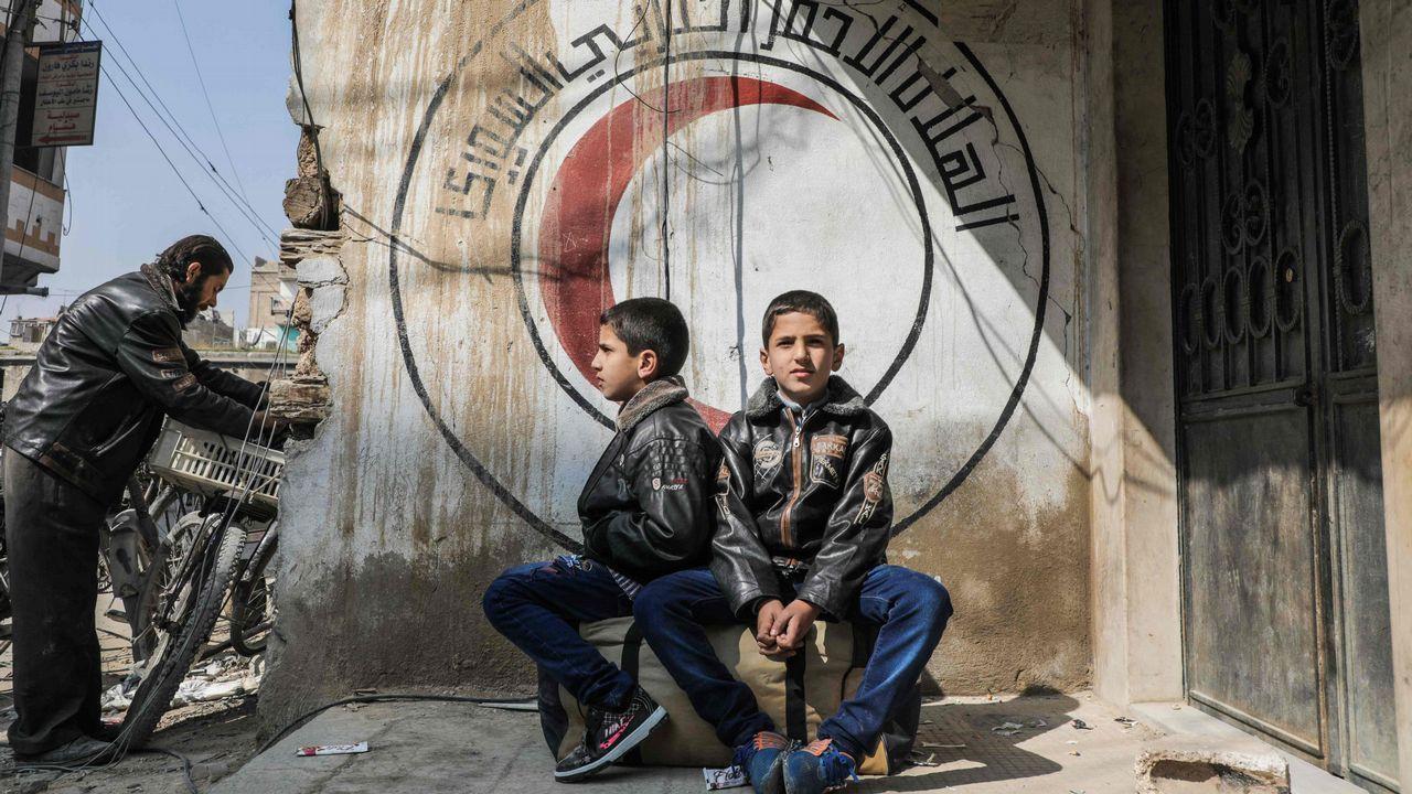Dos niños sirios sentados sobre una bolsa de viaje ante el logotipo de la Media Luna Roja en la ciudad de Guta