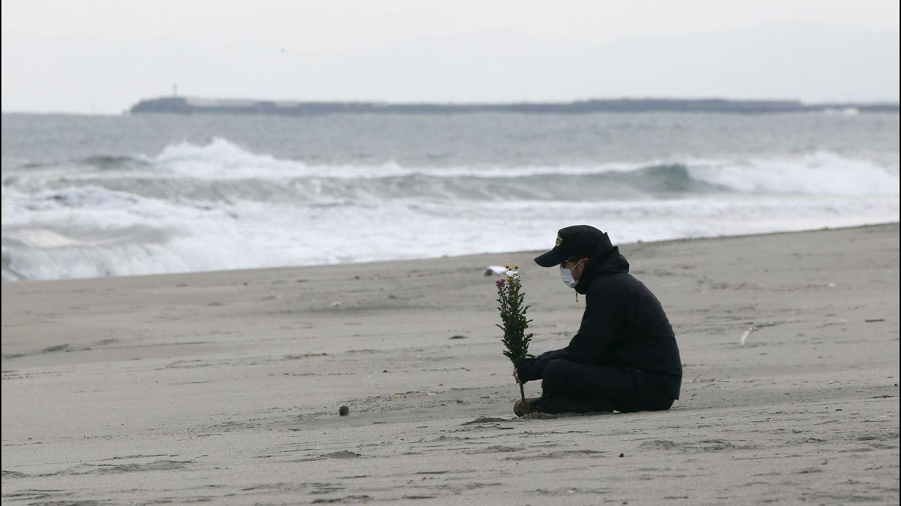 Un hombre sostiene un ramo de flores frente al mar en el aniversario del terremoto y posterior tsunami en Sendai, en el 2011
