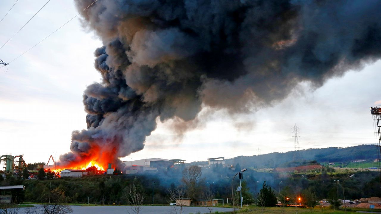 Los Bomberos de Gijón trabajan en las labores de extinción de un incendio producido esta tarde en una nave industrial ubicada en San Andrés de los Tacones (Gijón). El siniestro, en el que no se han producido daños personales, se originó por causas desconocidas en la empresa de desguaces Grupo Riestra