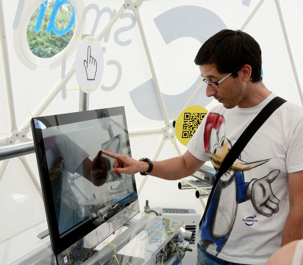 Un visitante examina un ordenador en una carpa de Smart City instalada en el Obelisco.