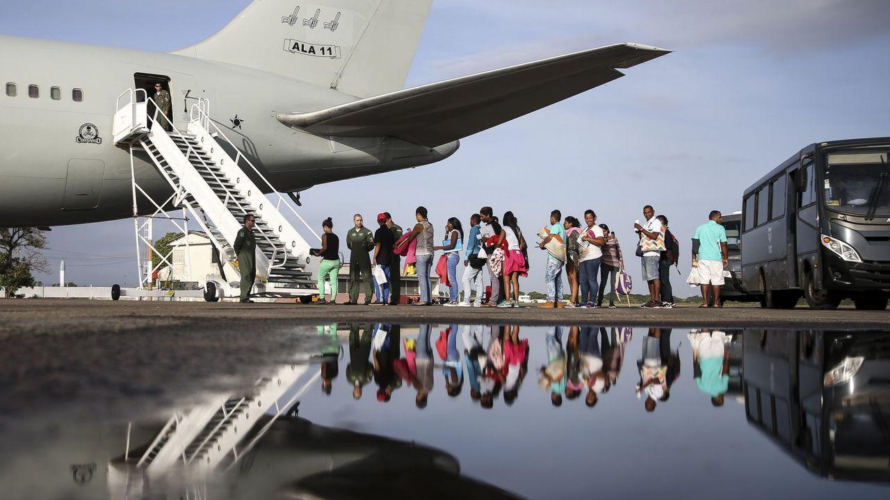 Migrantes venezolanos suben a una avión de las fuerzas aéreas brasileñas en el aeropuerto de Boa Vista para dirigirse a Manaos y Sao Paulo