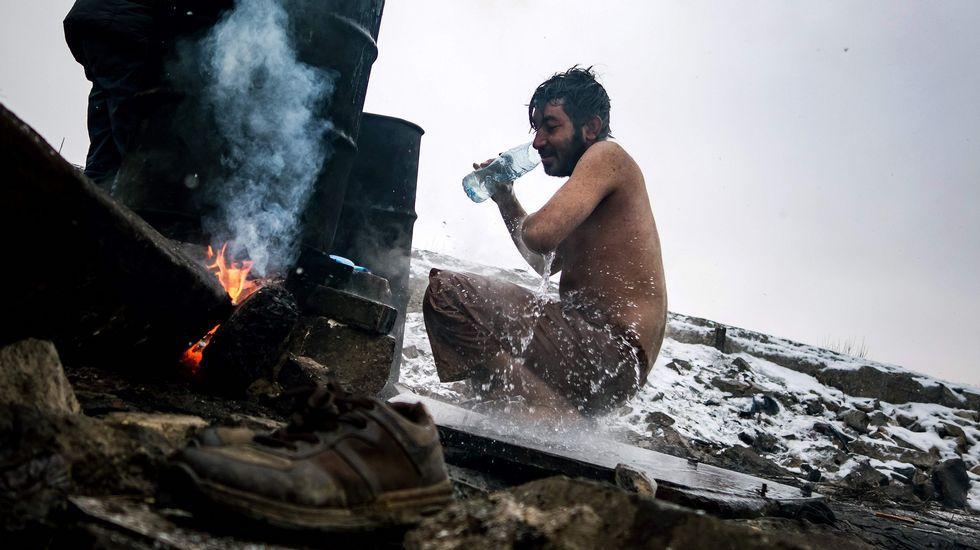 felicidadh.Un refugiado se lava fuera de un almacén abandonado usado como refugio cerca de la estación principal de tren de Belgrado (Serbia), donde se registran temperaturas bajo cero. Se calcula que alrededor de 7.000 refugiados están varados en Serbia.
