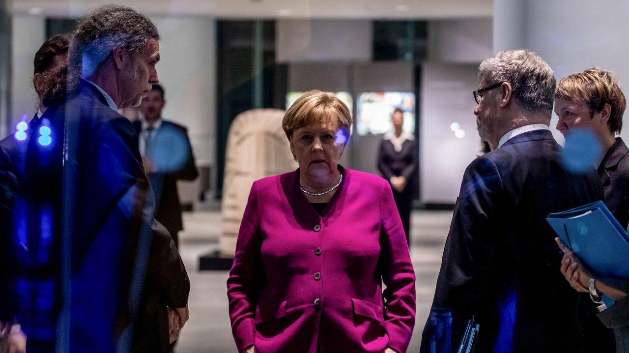 Merkel, escoltada por sus colaboradores, esperando en Berlín el inicio de un acto