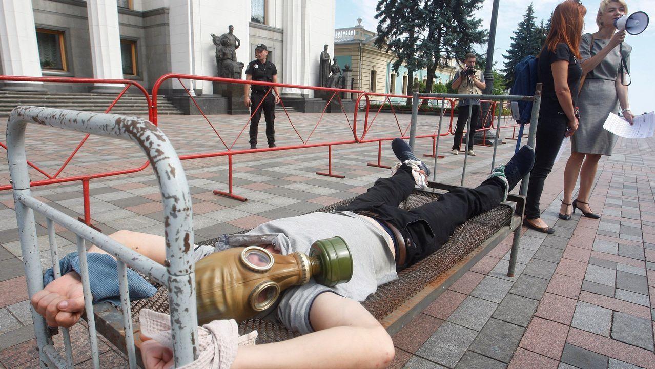 . Un activista ucraniano viste una máscara de gas durante una protesta contra la tortura en el Día Internacional de Apoyo a las Víctimas de la Tortura delante del Parlamento ucraniano en Kiev