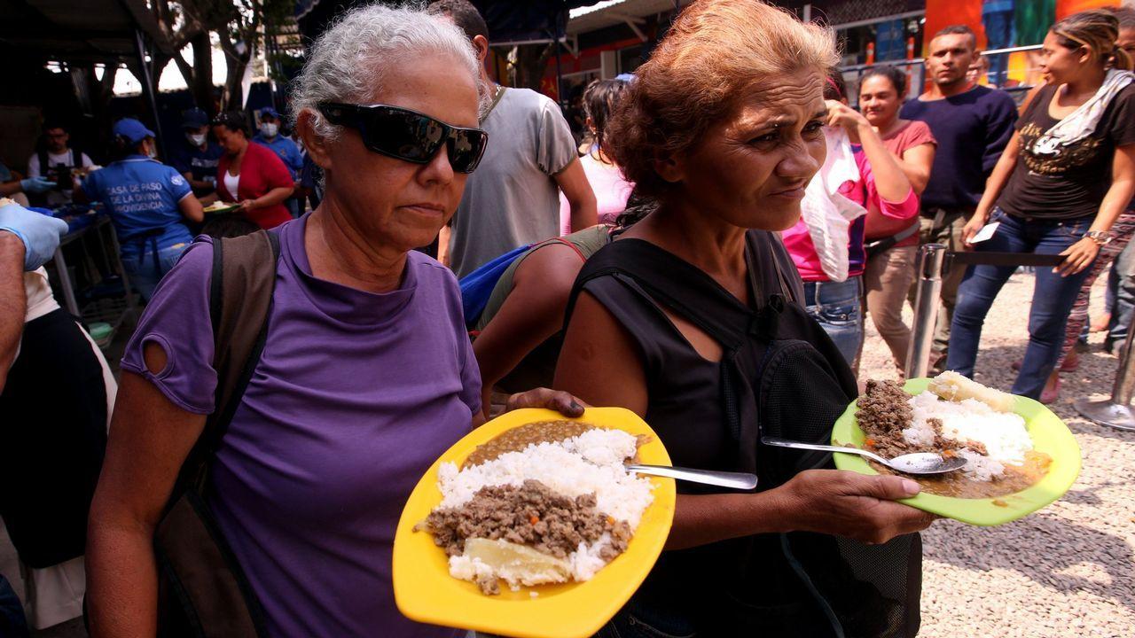 Un grupo de pasajeros consulta los vuelos en el Aeropuerto de Asturias.Ciudadanos venezolanos hacen fila para recibir una ración de comida en un comedor en Cúcuta (Colombia)