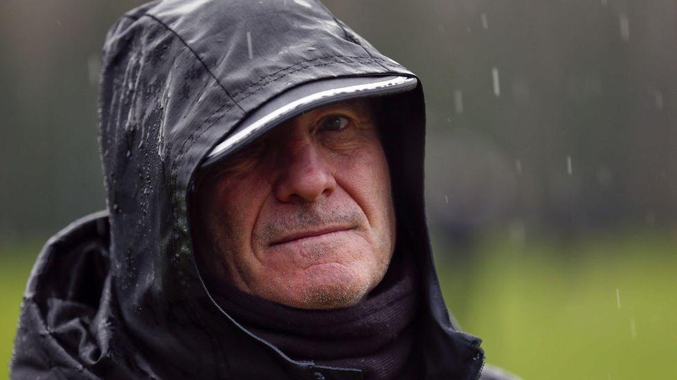 .El entrenador del Real Oviedo, Juan Antonio Anquela, bajo la lluvia durante un entrenamiento del equipo en El Requexón.