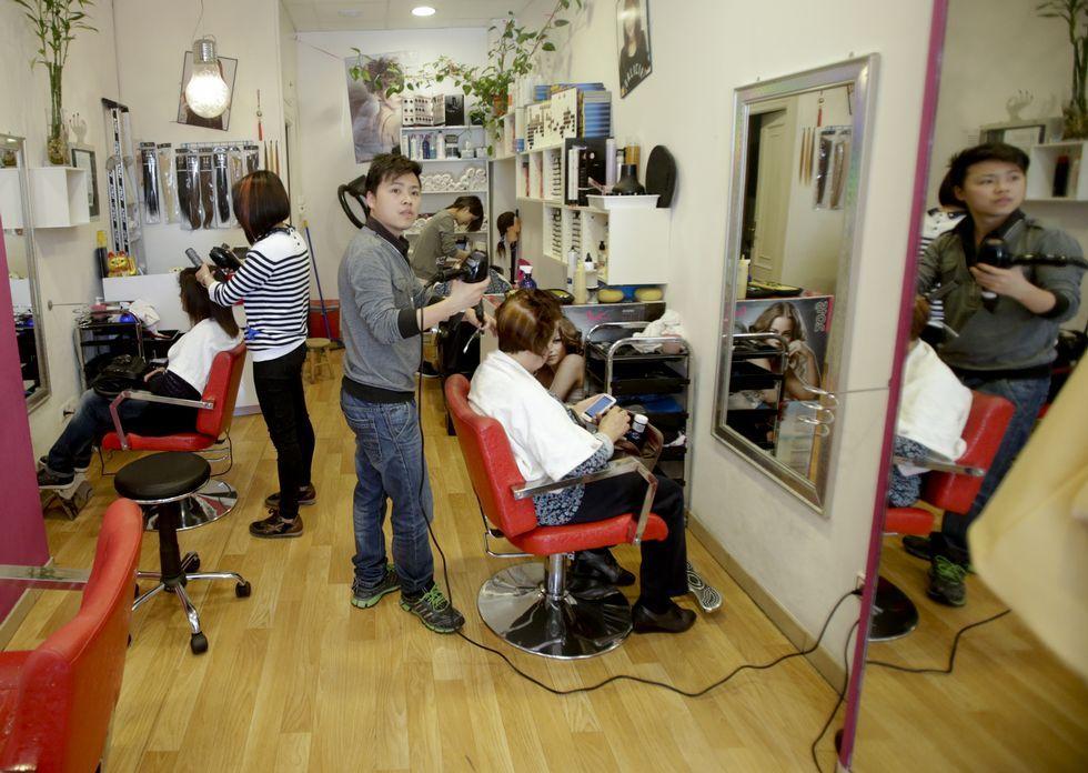 Qunwei Huang, propietario de la peluquería S. M. de la avenida Finisterre, peina a una clienta.