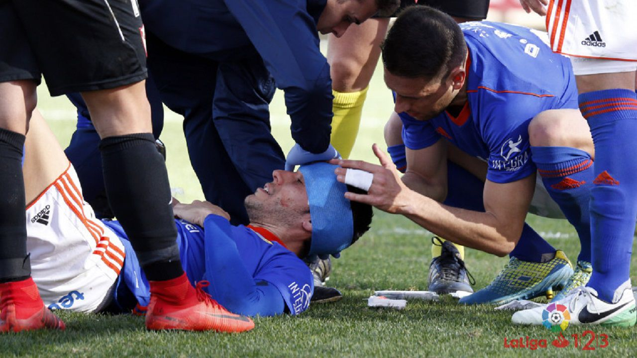 Folch Rocha lesion Real Oviedo Sevilla Atletico.Folch es atendido de una herida en la cabeza tras chocar con Carlos Hernandez