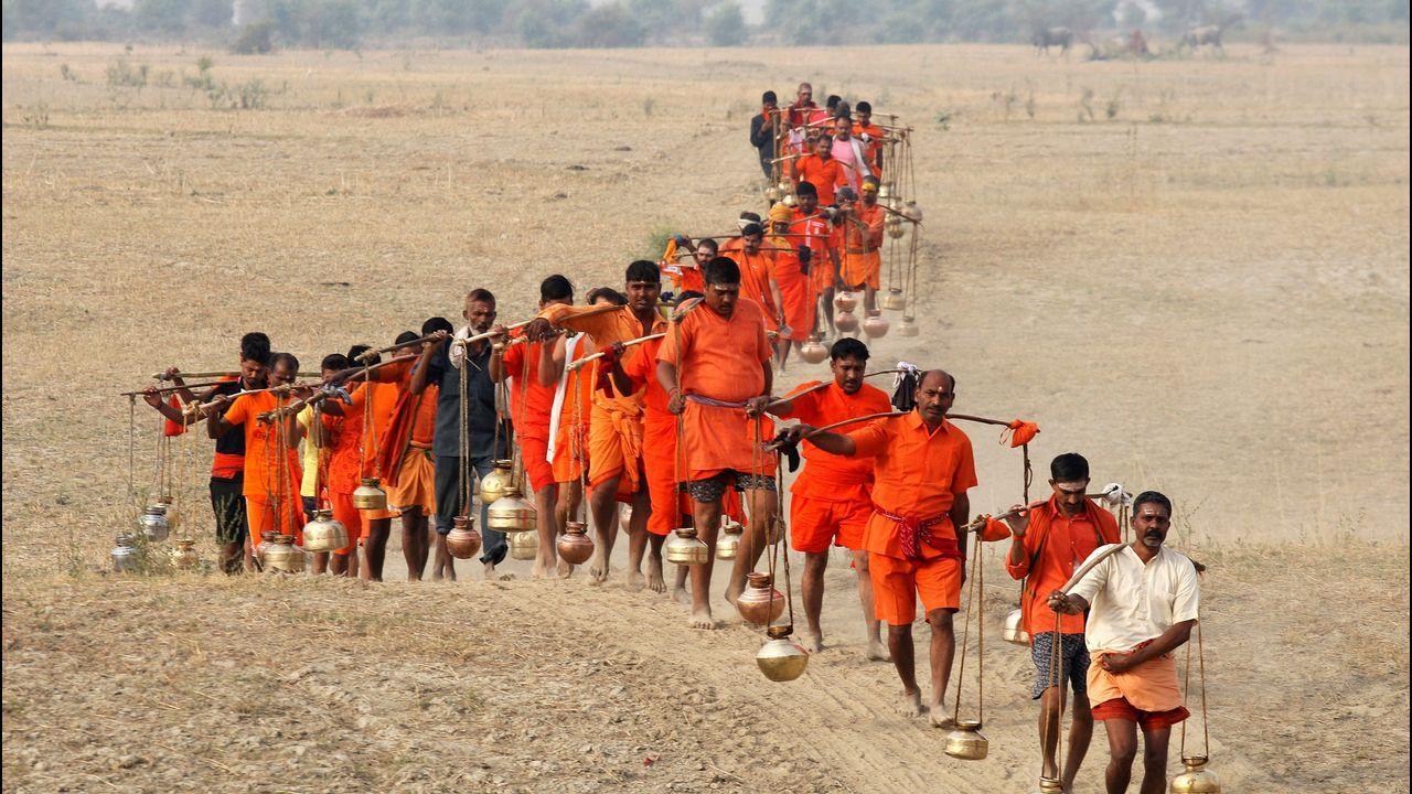 Un grupo de devotos cargan recipientes de metal con agua del río Ganges para hacer una ofrenda al dios Shiva