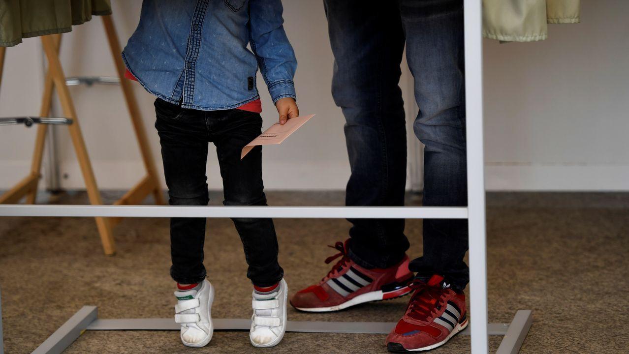 Un elector, con su hija, en una de las cabinas para elegir los votos, en Pola de Siero