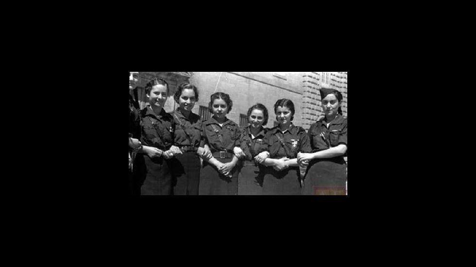 Mujeres con uniformes falangistas ante la fachada del Colegio de la Compañía