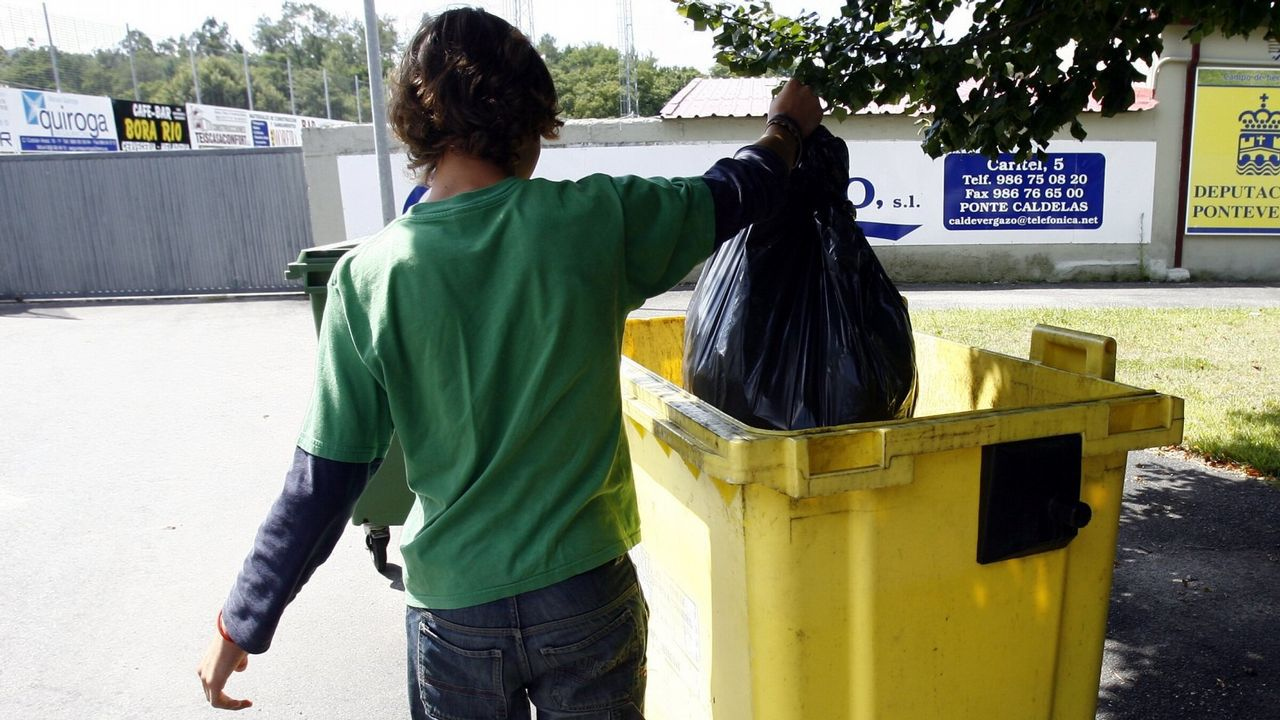 Un joven deposita una bolsa en el contenedor amarillo
