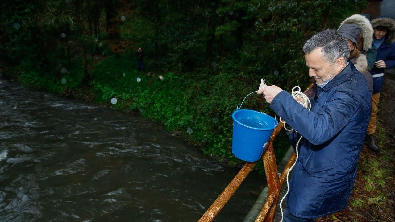 El portavoz del PP, Agustín Hernández, recoge una muestra del río Sar.