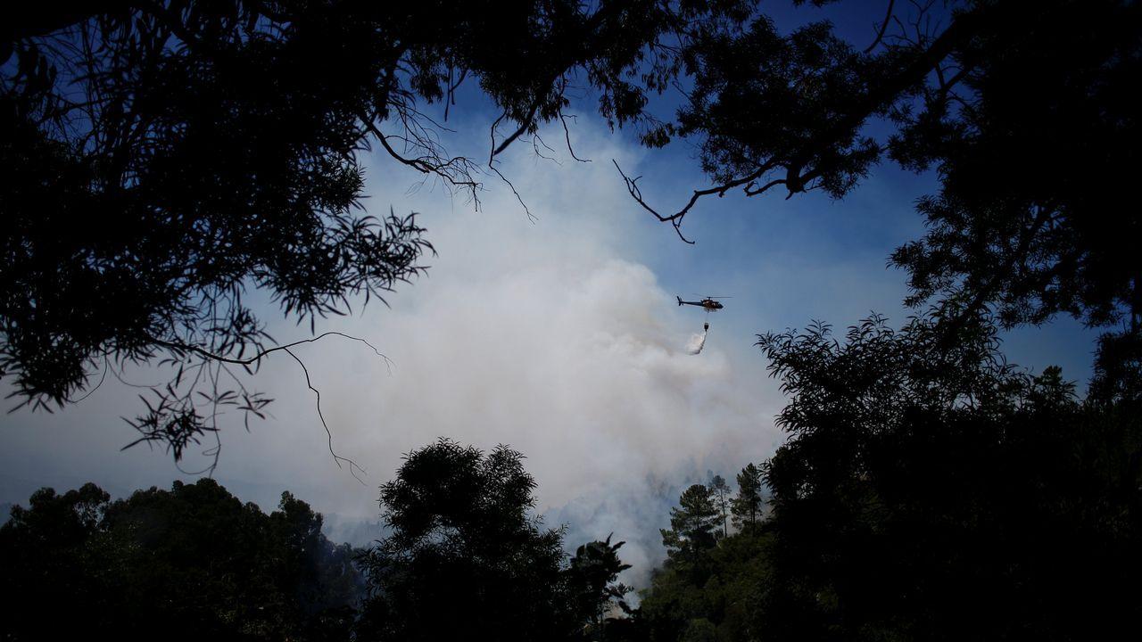 Un helicóptero tira agua sobre las llamas