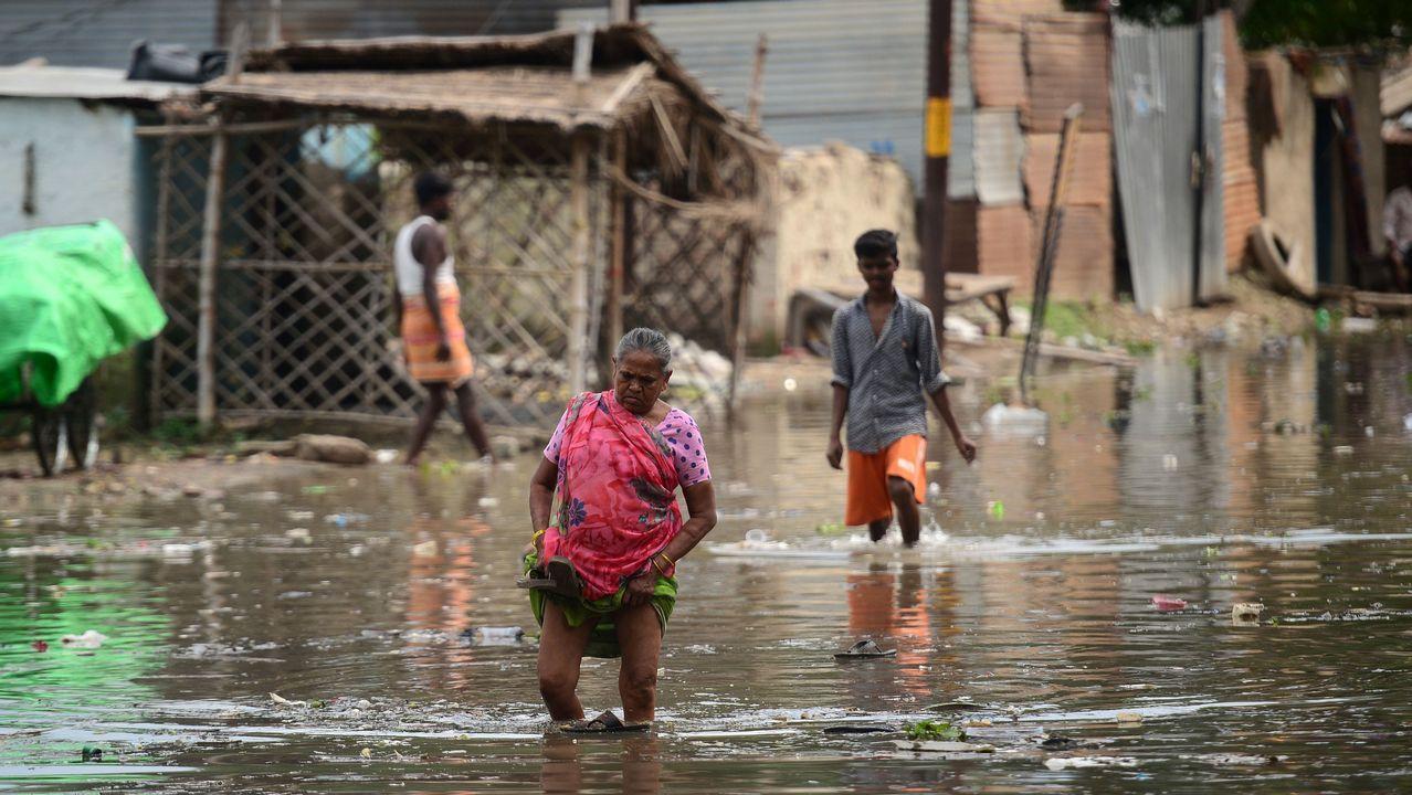 Vecinos de una barriada de Allahabad, en India, caminan por una calle inundada