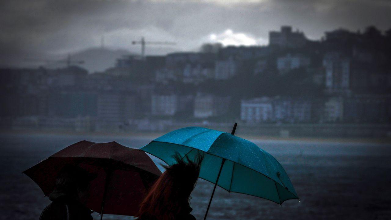 Dos mujeres caminan bajo la lluvia junto a la playa de Ondarreta de San Sebastián