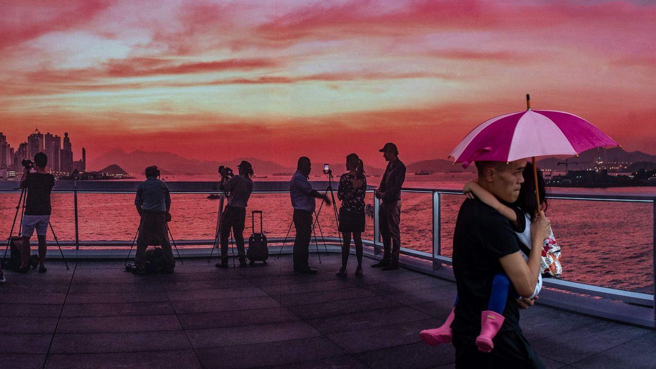 Un hombre lleva en brazos a su hija durante una puesta de sol en Hong Kong