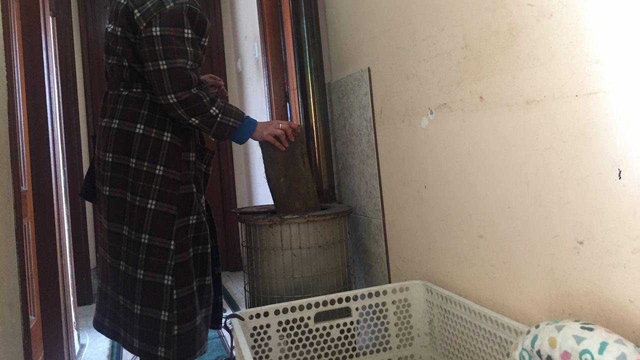 Sigue la búsqueda de Yulen en Totalán.Una mujer echa leña a la estufa con la que se calienta