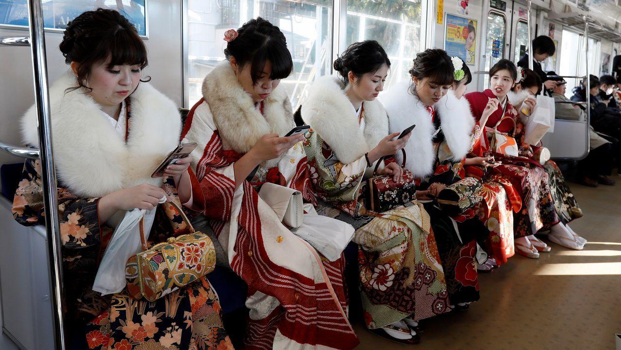 Jóvenes japonesas ataviadas con kimonos consultan sus móviles mientras regresan en tren tras participar en una fiesta en el parque de atracciones de Toshimaen de Tokio con motivo de su mayoría de edad, en Japón