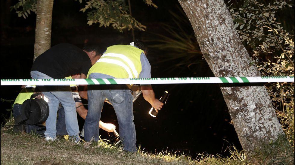 .Varias personas con linternas durante las operaciones de búsqueda del desaparecido.