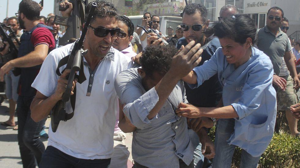 .Un policía controla la multitud que intenta agredir a un sospechoso de estar involucrado en el ataque al hotel Riu en Port el Kantaui en la costa tunecina.