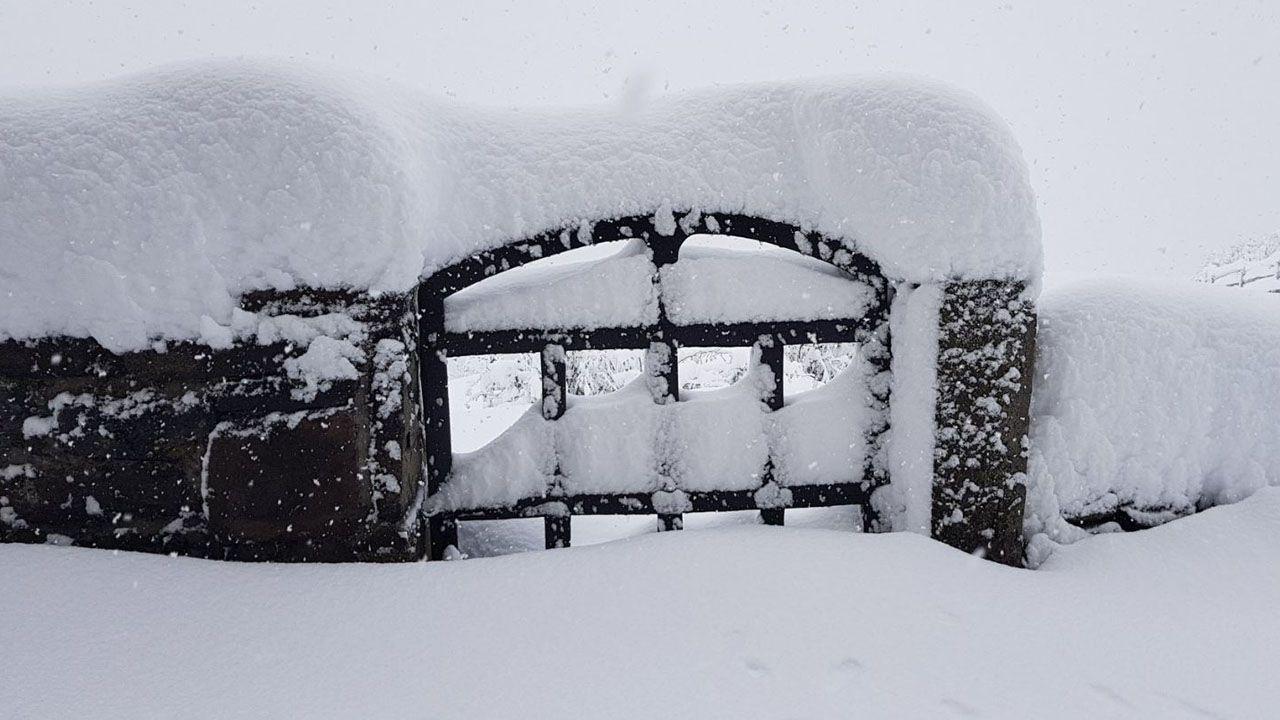 La puerta de una verja completamente cubierta de nieve en Pajares