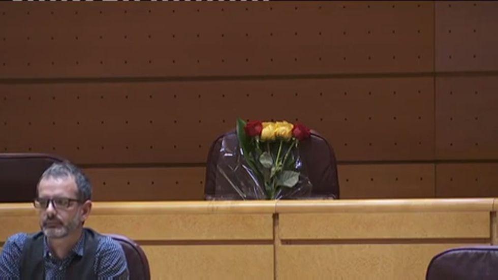 Un ramo de flores sobre el escaño de Rita Barberá en el Senado.Policías nacionales ante la sede del Tribunal Constitucional