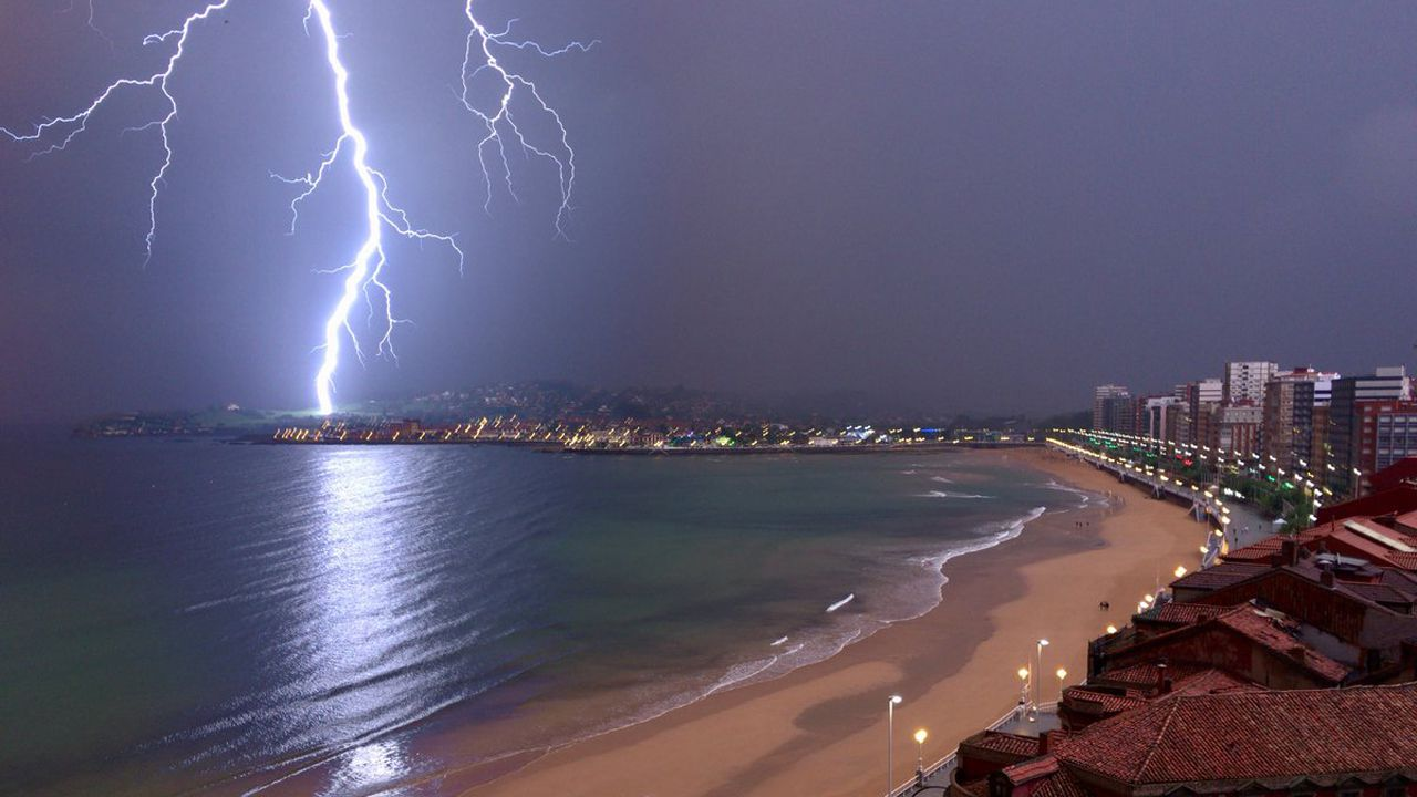 .Un rayo ilumina la playa de San Lorenzo, en Gijón