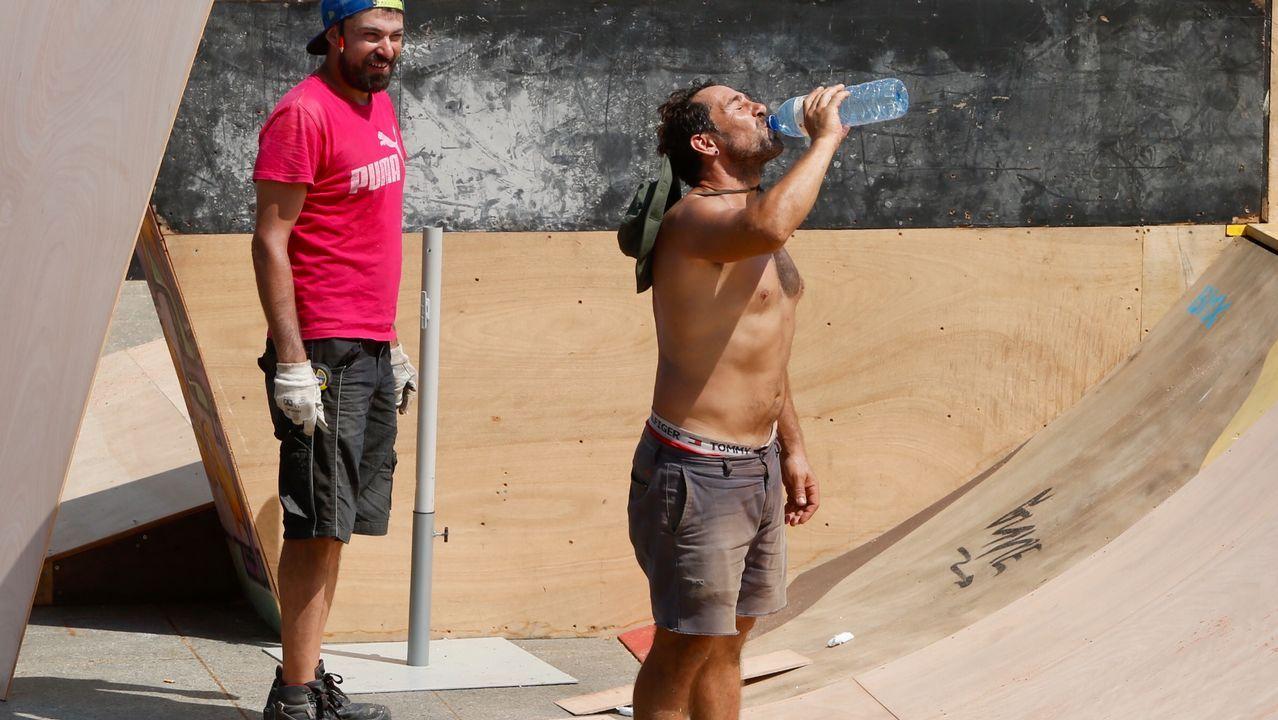 .Un trabajador se refresca mientras trabaja a pleno sol