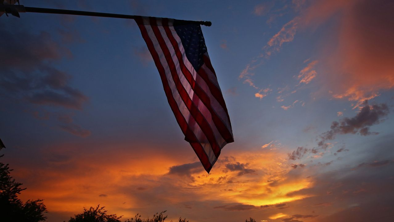 Vista del atardecer tras una bandera de EE. UU. en un pueblo de Texas