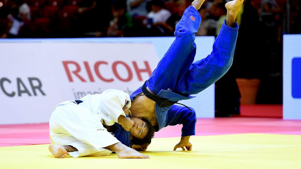 El medallista de oro japonés Ryuju Nagayama (izquierda, de blanco) pelea con el ruso Albert Oguzov (de azul) durante la final de categoría masculina de -60 kg del Gran Premio de Budapest del Circuito Mundial de Judo en Budapest
