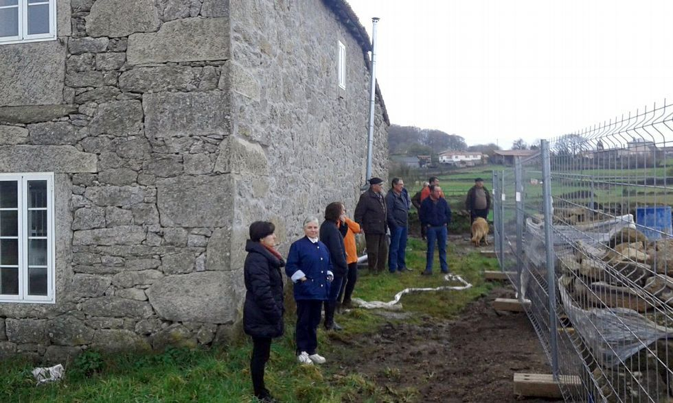 Un grupo de vecinos de Olveda delante de la casa escuela y las obras del cementerio.