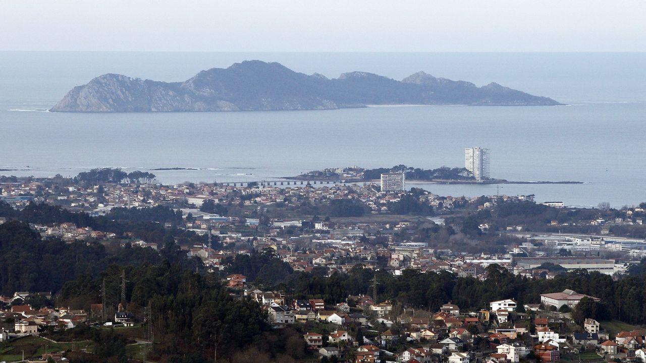El piloto de Iberia que promociona las Cíes.Un grupo de pasajeros consulta los vuelos en el Aeropuerto de Asturias