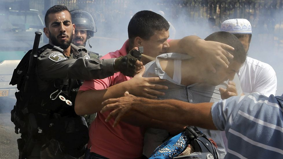 Batalla campal en Cisjordania.Dos palestinos enmascarados se cubren tras lanzar piedras contra los soldados israelíes.