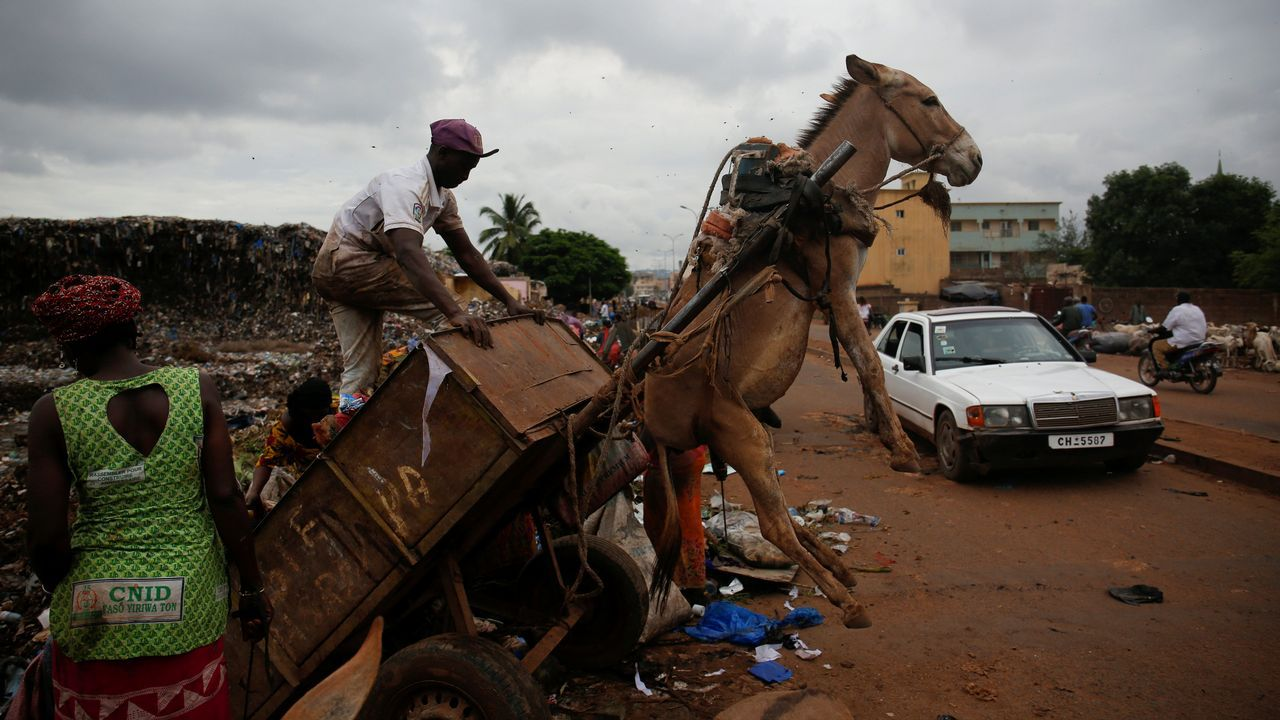 Un hombre descarga la basura que transporta en su carro en una estación de transferencia de desechos en Mali.