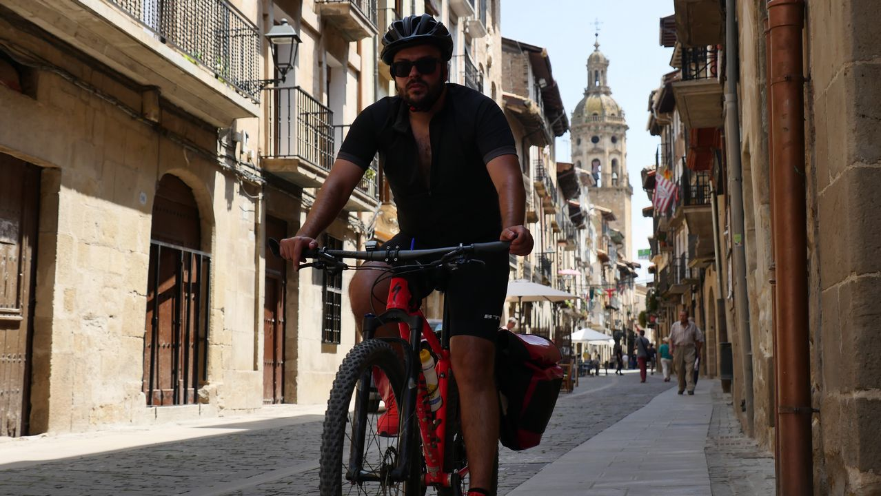Iago García, redactor de La Voz de Galicia, entrando en bicicleta en Puente La Reina