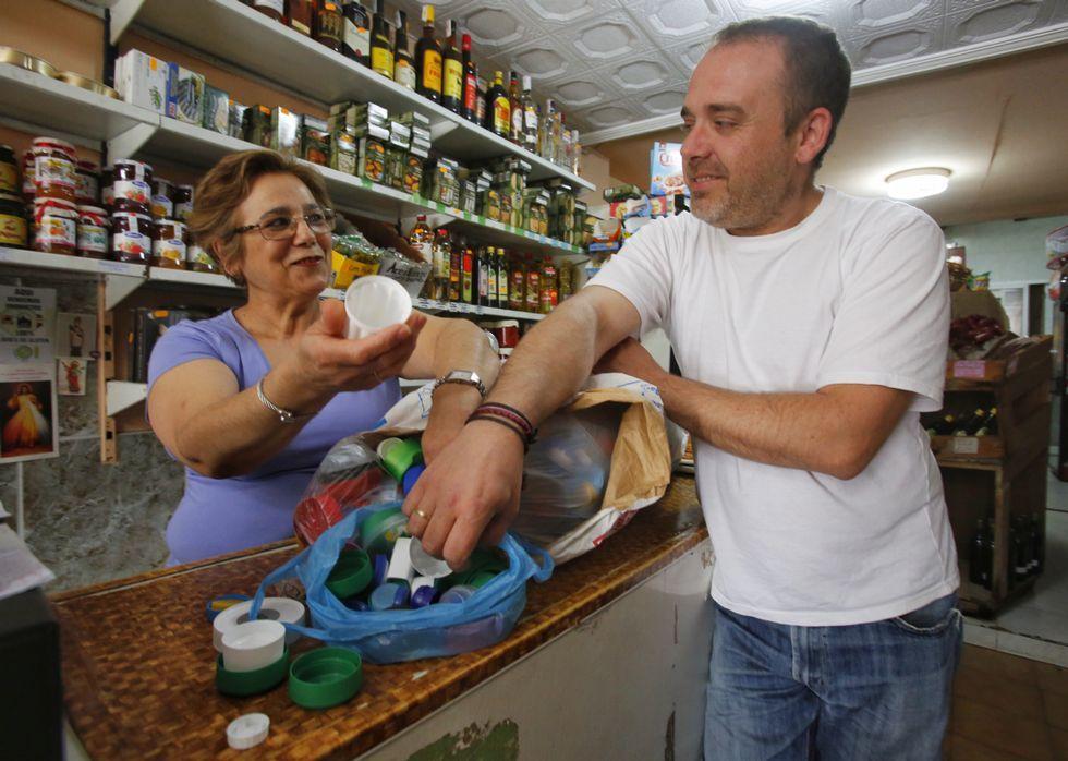 Ricardo, que recoge los tapones en varios concellos, ayer, en la tienda de María Luisa.