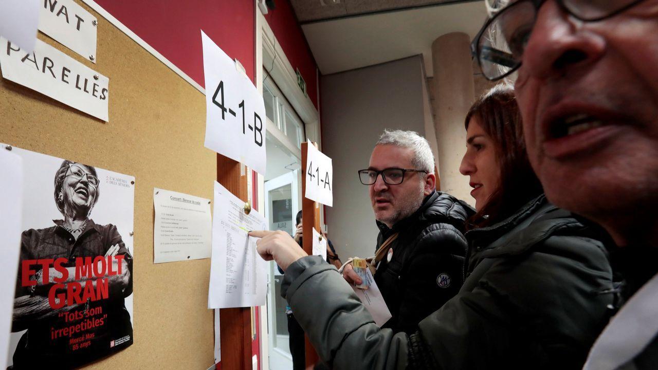 .Varias personas consultan el censo electoral en un colegio.