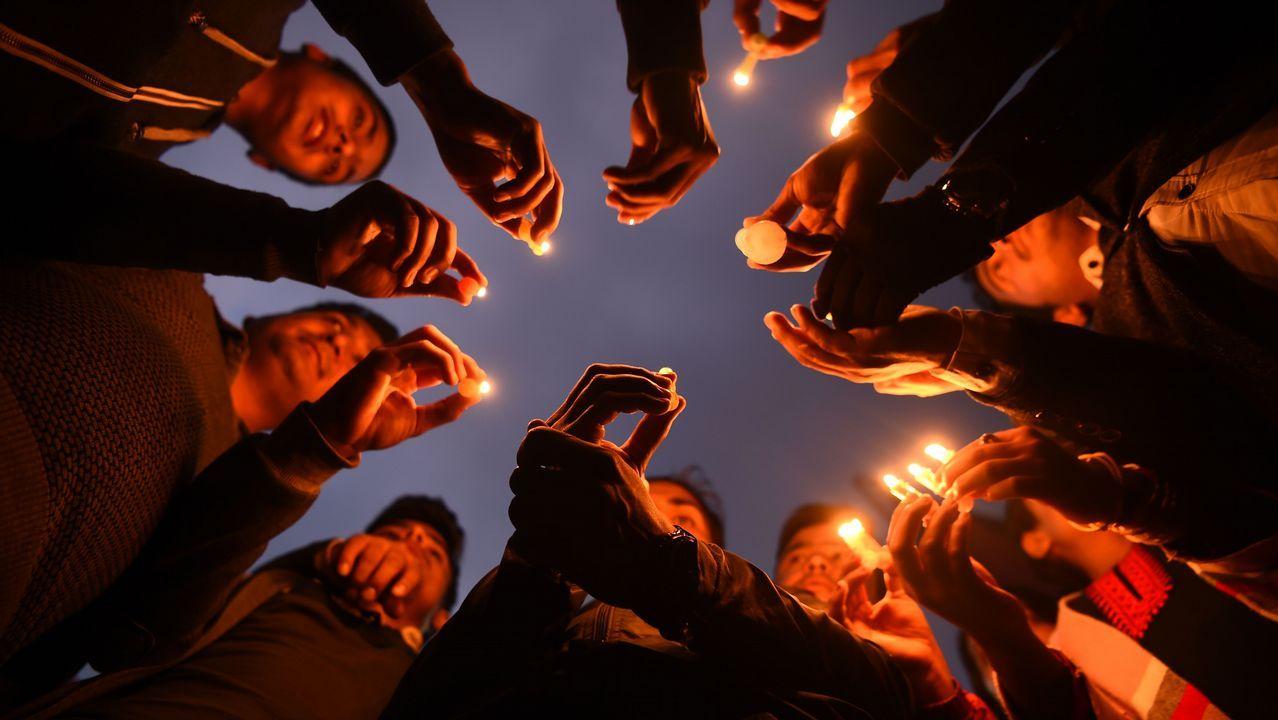 Un grupo de nepalíes encienden velas en homenaje a las víctimas del avión accidentado en Kadmandú