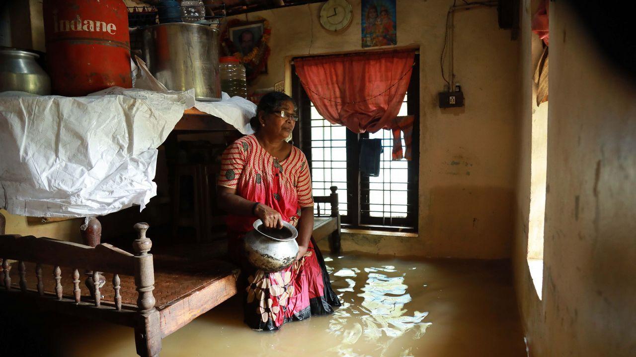 Una mujer india se sienta dentro de su casa, sumergida en las aguas del distrito Ernakulam de Kochi, en el estado indio de Kerala. Las inundaciones repentinas se cobraron al menos 27 vidas en el sureño estado indio de Kerala, lo que llevó a los EE. UU. a aconsejar a sus ciudadanos que se mantengan alejados del punto de acceso turístico.