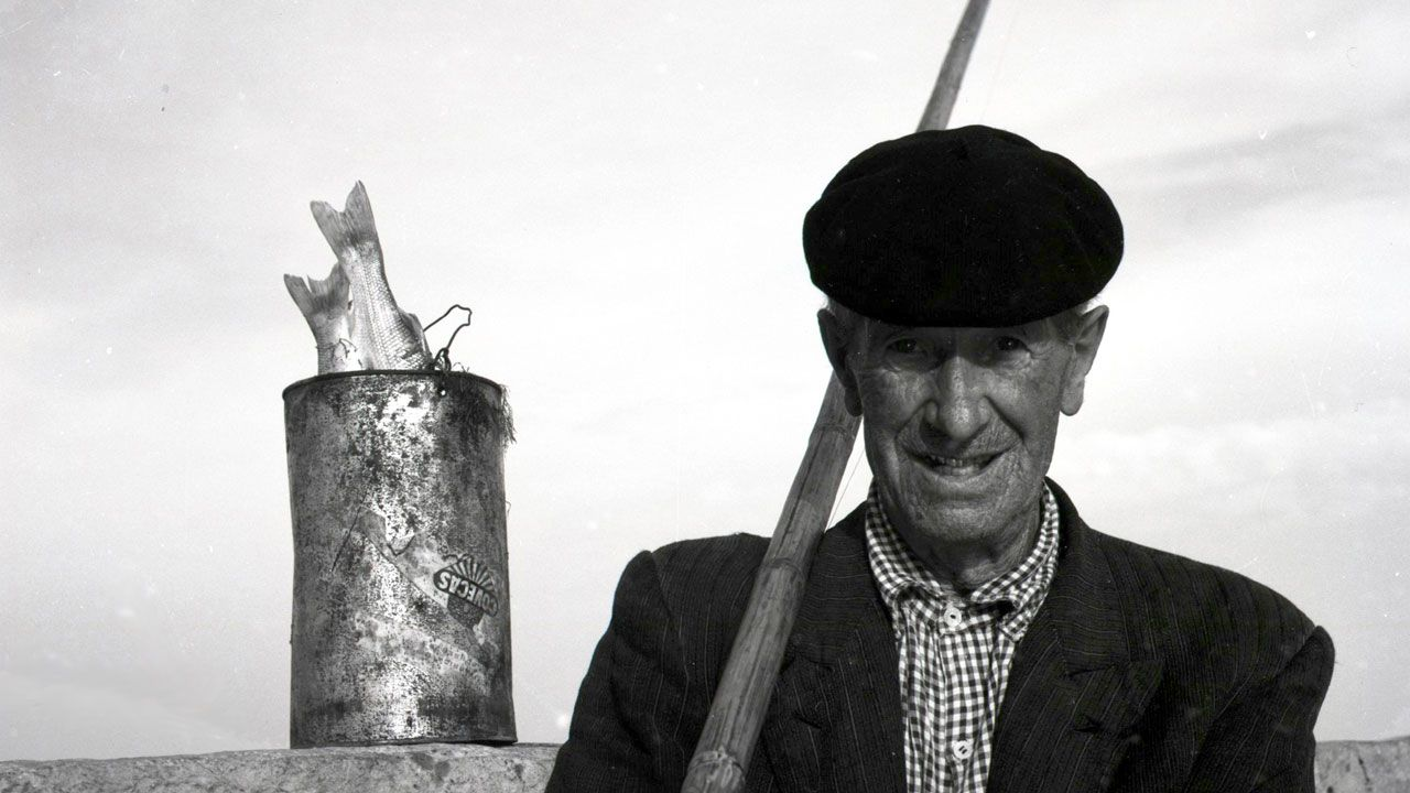 Pescador de caña en el muelle de Gijón