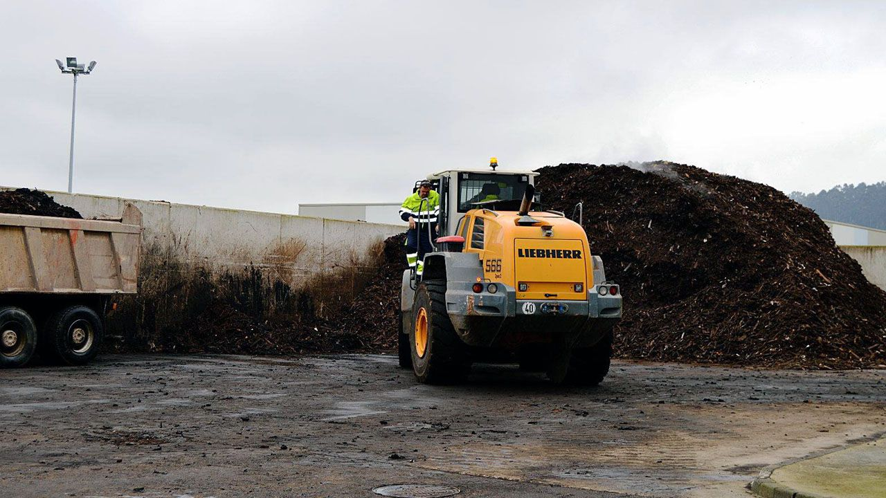 Una maquina trabaja con una pila de basura en el vertedero de Cogersa