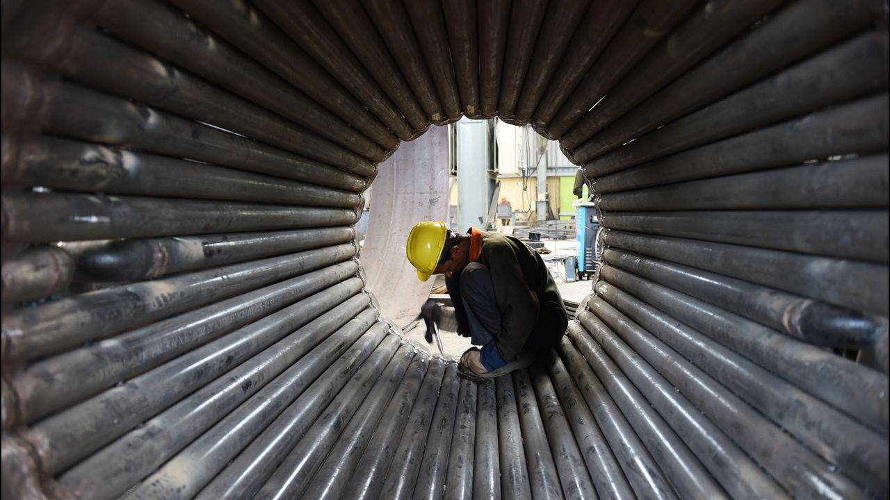 .Un operario trabaja en una estructura de metal después de participar en un ejercicio de yoga durante el día mundial de esta práctica, en Ahmedabad (India)