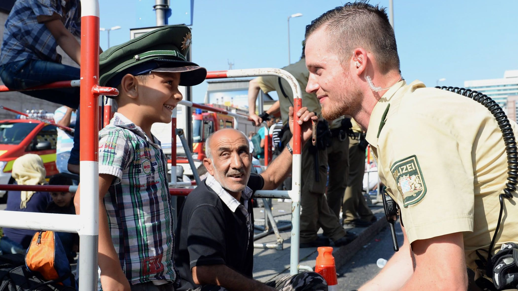 | EFE.Un policía alemán con refugiados sirios en Múnich, en la crisis migratoria del 2015