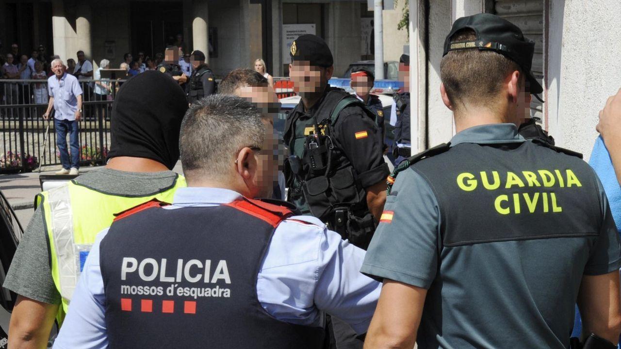 El policía nacional muestra el chaleco antibalas que le compró su madre para patrullar.