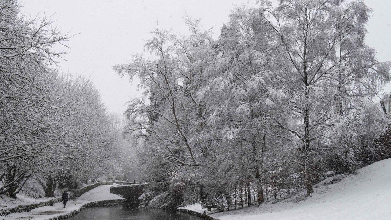Un hombre camina sobre la nieve junto a un canal de Mansden, en Reino Unido