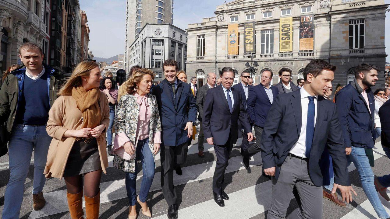 El presidente del PP, Pablo Casado (4i), y la candidata del PP a la Presidencia del Principado, Teresa Mallada (3i), pasan frente al teatro Campoamor de Oviedo tras la firma del acuerdo por el que PP y Foro Asturias concurrirán en coalición a las elecciones generales del 28 de abril.