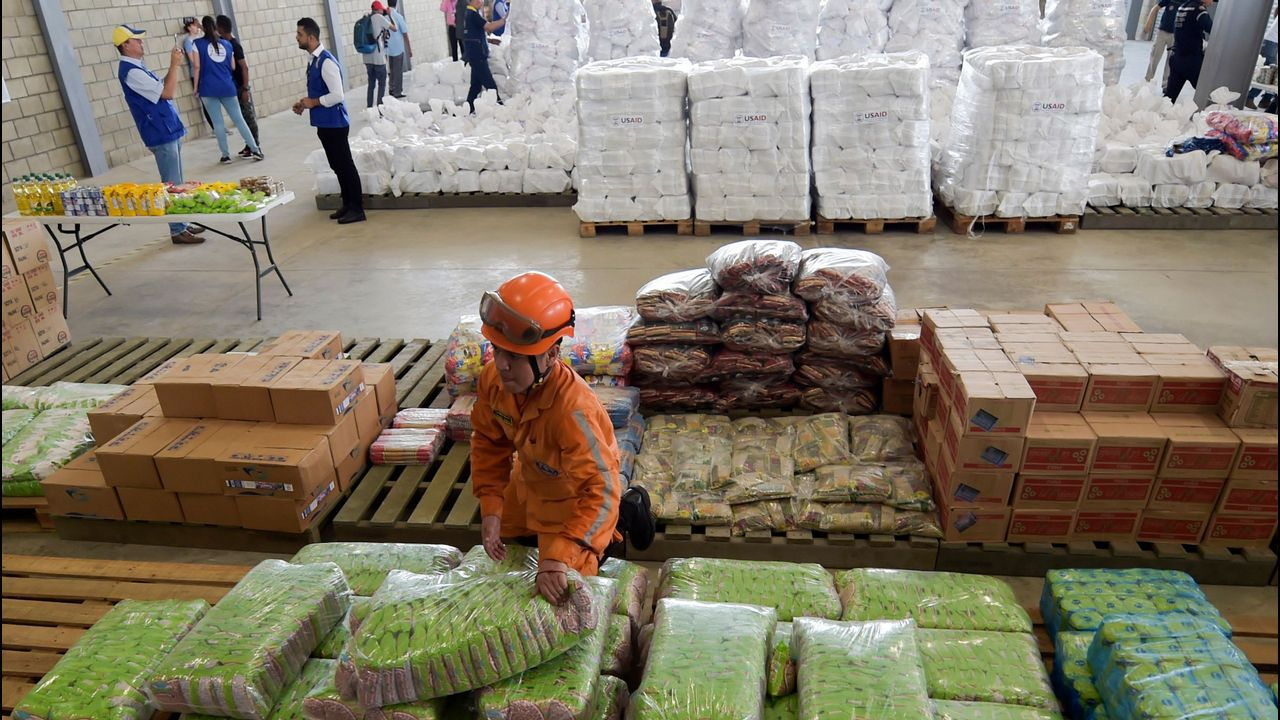 Miembros de la Defensa Civil colombiana organizan la ayuda estadounidense que se acumula en un almacén de Cúcuta